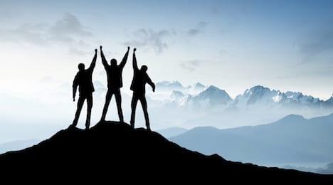 A team on mountain peak symbolising successful program execution.