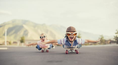 A young boy and girl are wearing flying goggles while outstretching their arms to attempt flying while on skateboards. - symbolising a quick start of a start-up business